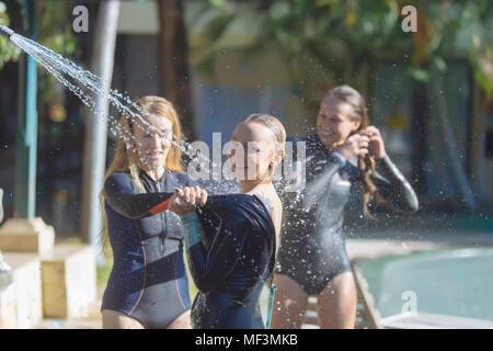 Indonesia, Bali, femmina surfers sotto la doccia Foto Stock