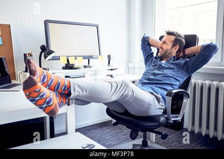 Rilassata uomo seduto alla scrivania in ufficio guardando lo schermo del computer Foto Stock
