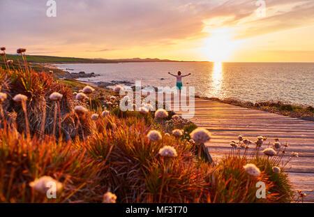 L'Italia, Sardegna, Lu Litarroni, senior donna sulla passerella in legno al tramonto Foto Stock
