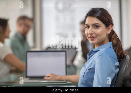 Ritratto di imprenditrice sorridente con notebook durante una riunione in ufficio boardroom Foto Stock
