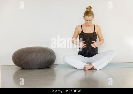 Donna incinta seduta su un materassino yoga Foto Stock