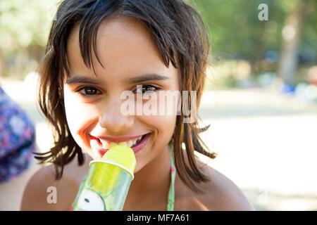 Carino e felice bambina di mangiare un lime ghiaccio crema dopo siwimming in piscina Foto Stock