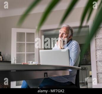 Malinconici uomo maturo seduta a tavola con il computer portatile nel suo salotto Foto Stock