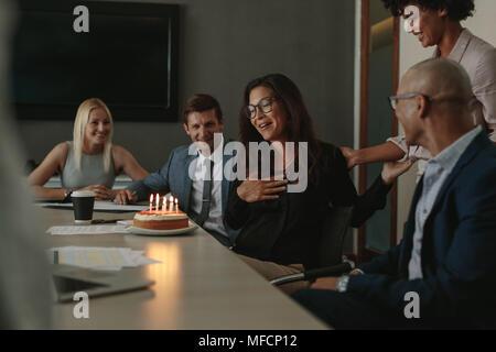 Gli impiegati celebrando collega il compleanno durante una riunione nella sala conferenze. Il team Aziende per celebrare il compleanno di colleghi in ufficio Foto Stock