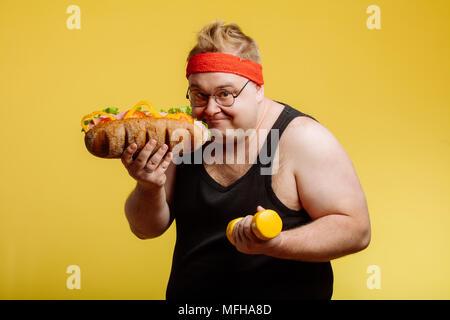 Ritratto di uomo felice preparare da mangiare hamburger e guardare la fotocamera