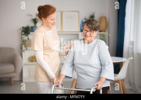Professional medical custode in uniforme contribuendo sorridente donna senior con un walker in un soggiorno di lusso privata clinica sanitaria Foto Stock