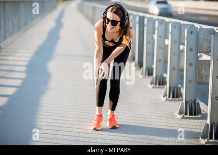 Donna con il trauma del ginocchio durante la corsa mattutina Foto Stock