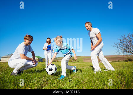La famiglia felice giocando con una palla sulla natura in primavera, d'estate. Foto Stock