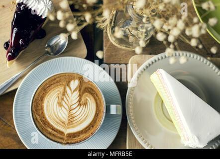 Cappuccino con caffè e latte art e fetta di torta dessert Foto Stock