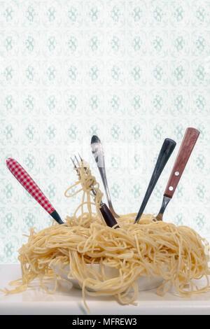 Una piastra piena di spaghetti con cinque forcelle Foto Stock