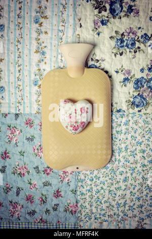 Un caldo-acqua in bottiglia su un letto d'annata con un cuore floreale Foto Stock