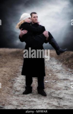 Un uomo porta la sua ragazza su un prato Foto Stock