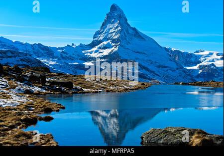 Snowy Matterhorn riflessa nella parzialmente congelato Stellisee, Zermatt, Vallese, Svizzera Foto Stock