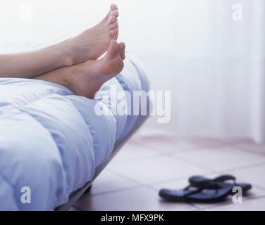 Close up della donna? A piedi nudi poggiante sulla estremità del letto con coppia di flip flop sul pavimento. Foto Stock