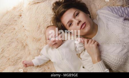 Madre e figlia neonato giacciono su una rosa plaid. Essi sono vestiti in caldo bianco a maglia Maglioni. La madre e il bambino giacciono affiancati. Tempo per la famiglia Foto Stock