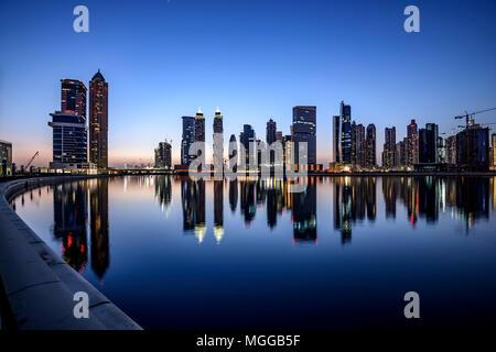 Downtown Dubai, Dubai riflettendo sul canale d'acqua con le luci della città, Emirati Arabi Uniti - NL Foto Stock
