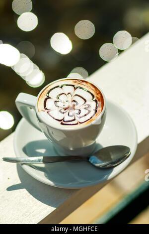 Caffè caldo cappuccino in tazza bianca.Il caffè di mattina. bianco tazza di latte caldo con caffè foglia, fiore pattern, latte art. Tazza da caffè Foto Stock