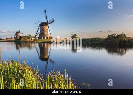 Tramonto sul mulino a vento si riflette nel canale Kinderdijk Molenwaard South Holland Olanda Europa Foto Stock
