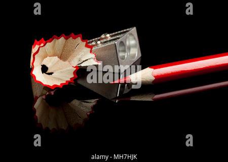 Affilare matita rossa con sharpener e scaglie riflettenti sulla superficie nera Foto Stock