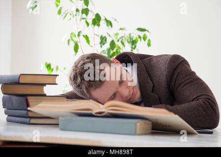 Un uomo in un business suit si è addormentato su una scrivania Foto Stock
