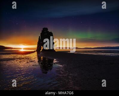 Cielo stellato e luci del nord in una spettacolare roccia nel mare sulla costa settentrionale dell'Islanda. Leggende dicono che è un troll pietrificato Foto Stock