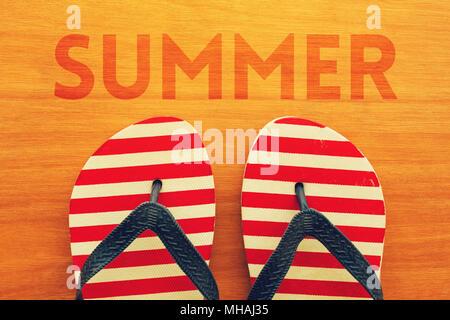 Vacanze estive stagione è qui. Spiaggia di sandali infradito con testo estate su sfondo di legno Foto Stock