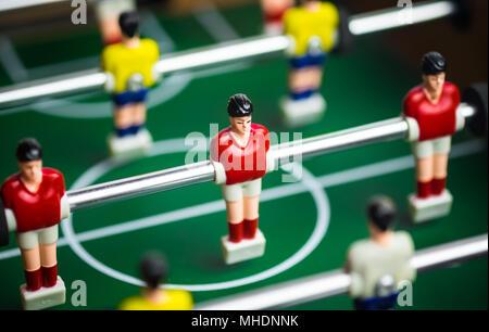 Chiusura del giocatore sul mini gioco di calcio su tavola, il concetto di lotta in business, vignette effetti filtro e messa a fuoco selettiva. Foto Stock