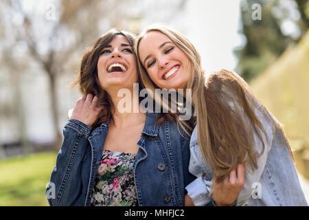 ... Due lieti di donne giovani amici abbracciando in strada. Bionda e bruna  le ragazze che b52c85998688