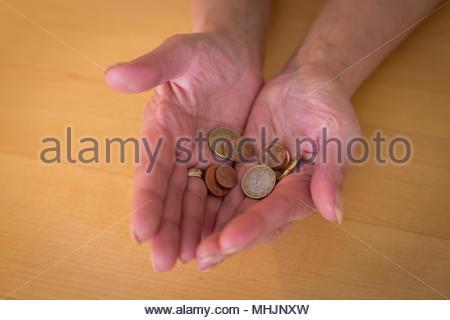 Donna che mantiene monete sparse nelle sue mani a tazza Foto Stock