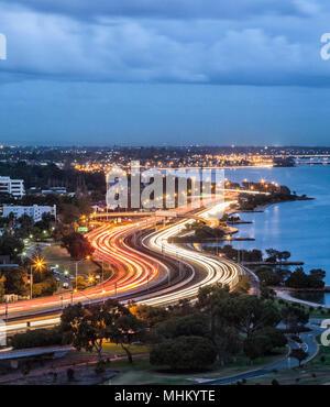 Sentieri di luce su una trafficata autostrada Mitchell al crepuscolo. Foto Stock