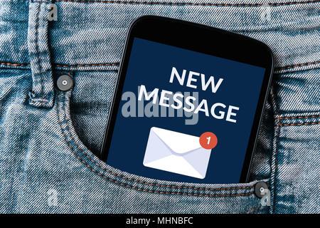 Notifica di un nuovo messaggio concetto sulla schermata dello smartphone in tasca dei jeans. Tutti i contenuti della schermata è progettato da me. Foto Stock