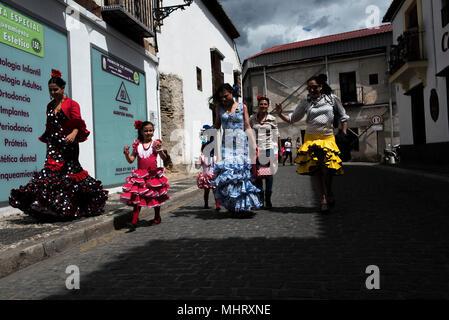 """Donne che indossano tipico abito di flamenco a piedi lungo le strade del quartiere Albaicin. """"El Día de la Cruz"""" o """"Día de las Cruces"""" è una delle più belle feste in Granada. Ogni 3 maggio molte vie, piazze e terrazze mostrano altari con croci ornate di fiori per commemorare la Santa Croce. Foto Stock"""