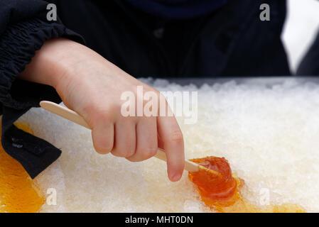 Close up di un giovane (5 anno di età del bambino la laminazione a mano lo sciroppo d'acero taffy su un bastone