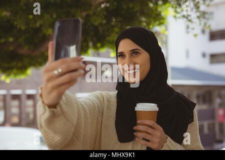 Il hijab donna prendendo selfie con telefono mobile
