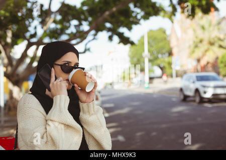 Il hijab donna parlando al telefono cellulare mentre avente un caffè a pavement cafe