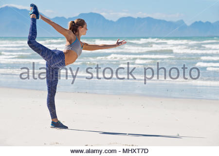 Donna in Sportswear stretching prima di esercitare sulla spiaggia in Sud Africa Foto Stock