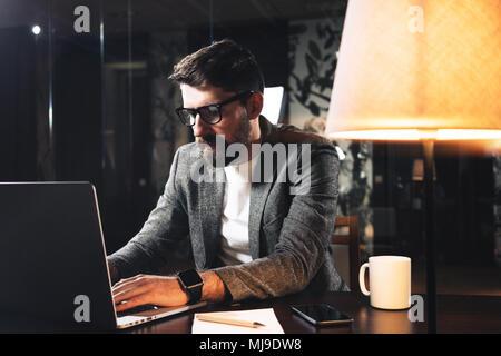 Giovane imprenditore barbuto seduti al tavolo di legno con lampada in ufficio loft di notte. Project manager del processo di lavoro e la digitazione del testo sul contemporanea n Foto Stock