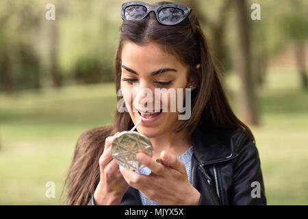 Ritratto di giovane donna che compongono se stessa in background urbano Foto Stock