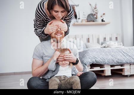 La famiglia felice madre, padre e figlia del bambino a casa Foto Stock