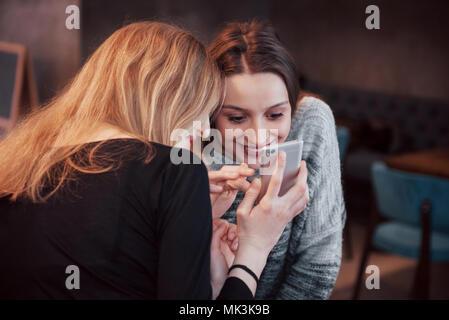 Due amici sorridenti lettura divertente la chat online su telefono moderno seduta con gustosi caffè nel ristorante.Hipster ragazze godendo di tempo libero nel bar con bevande calde e messaggistica su cellular Foto Stock