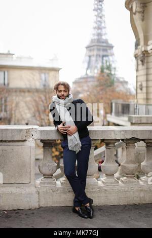 Afro American bel giovane uomo in piedi vicino alla ringhiera di cemento con la Torre Eiffel sullo sfondo di Parigi. Foto Stock