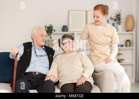 Assistente professionale supporto e consolante preoccupato senior coppia sposata in un soggiorno di un centro di assistenza Foto Stock