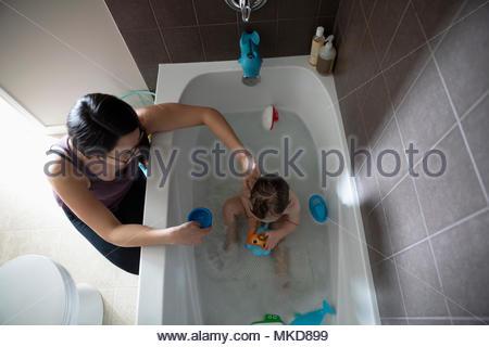 Madre di balneazione figlio bambino tenendo bagno, giocando con i giocattoli in vasca da bagno Foto Stock