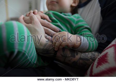 Close up affettuoso, tenero padre cuddling figlio bambino Foto Stock
