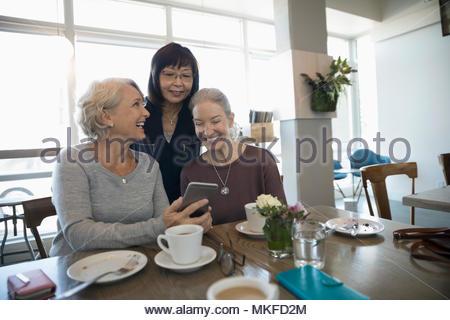 Sorridente active senior donne amici utilizzando smart phone e di bere il caffè nella caffetteria Foto Stock