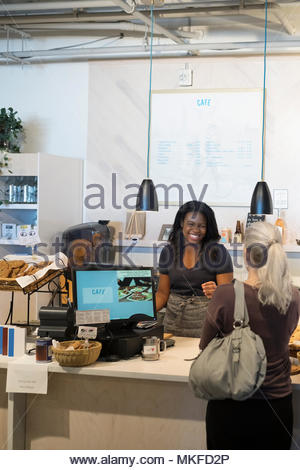 Lavoratore di sesso femminile che aiuta il cliente a forno Foto Stock