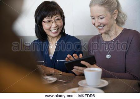 Sorridere le donne anziane utilizzando smart phone in cafe Foto Stock