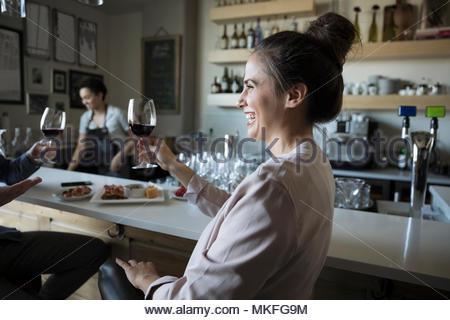 Ridendo, spensierata giovane donna di bere il vino rosso in bar Foto Stock