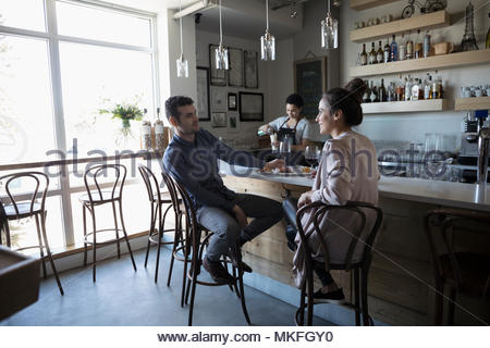 Coppia giovane sulla data e di bere il vino rosso in bar Foto Stock
