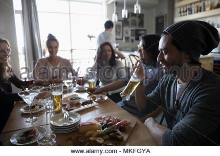 Giovani amici godendo di happy hour presso il bar tavola, bere birra e cocktail Foto Stock